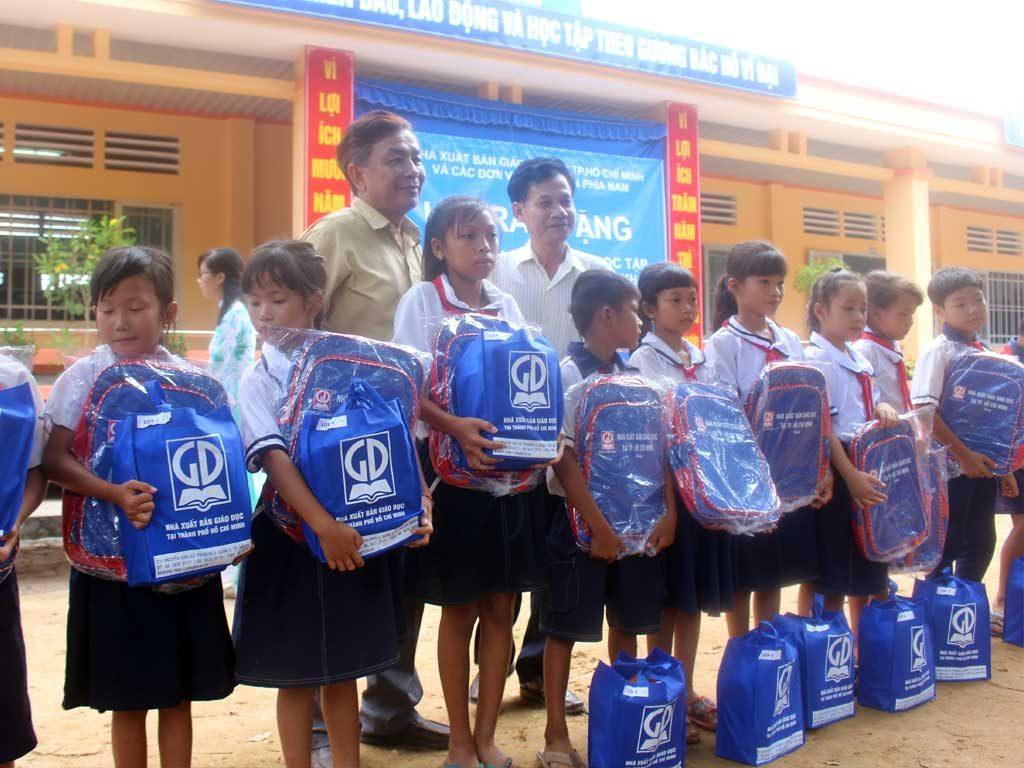 Ông Đỗ Thành Lâm - PGĐ NXB Giáo Dục tại TP. HCM và ông Trúc Lâm - Phó ban tuyên giáo Huyện Tân Châu trao quà cho các em học sinh trường TH Đồng Kèn - Huyện Tân Châu