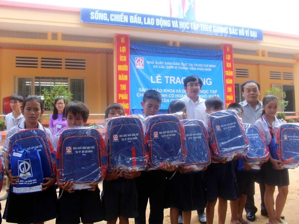 Ông Ngô Đoàn Trọng Nghĩa - PGĐ NXB Giáo Dục tại TP. HCM và đại diện chính quyền địa phương trao quà cho các em học sinh trường TH Đồng Kèn - Huyện Tân Châu