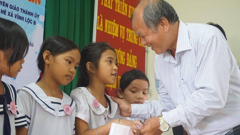Ông Trần Văn Hưng - Phó GĐ NXBGD tại TP.HCM tặng SGK cho các em HS tại xã Vĩnh Lộc B - Huyện Bình Chánh