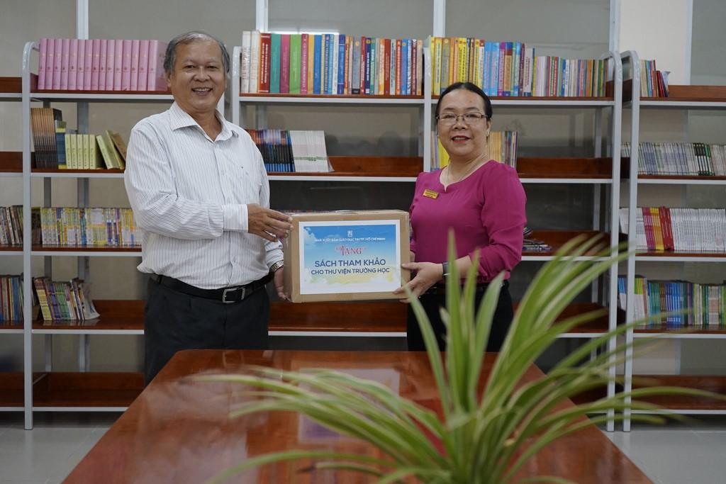 Ông Trần Văn Hưng - PGĐ NXBGD tại TP. HCM (trái) trao tặng STK cho đại diện trường TH Nhị Tân - Huyện Hóc Môn